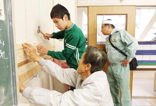 指導を受けて真剣に作業をする児童たち